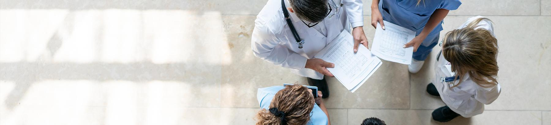 Overhead view of doctors and nurses discussing patient charts