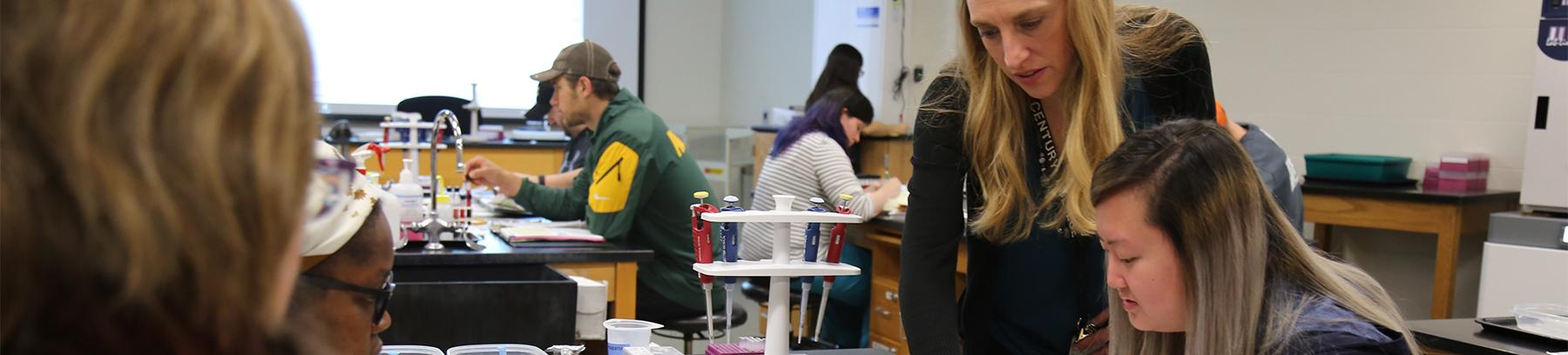 Instructor assisting students in a science lab.
