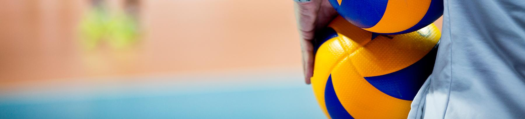 Close up of a person holding a volleyball.