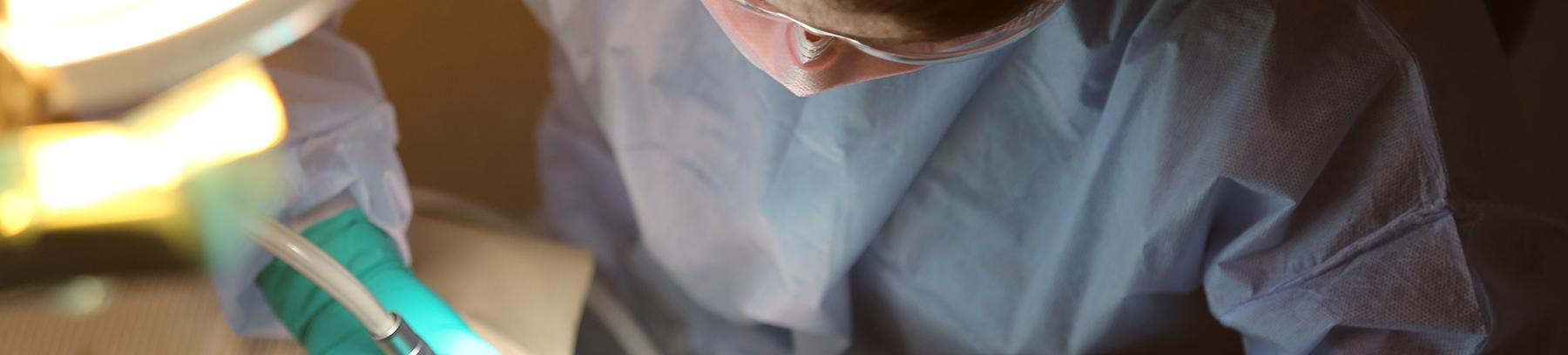 Close up of a student wearing googles and a mask holding dental equipment.