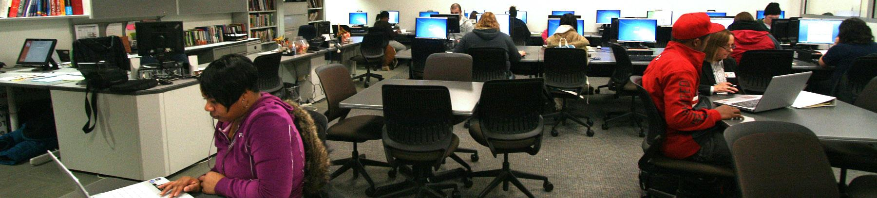 Image of computer room and students working on computers.