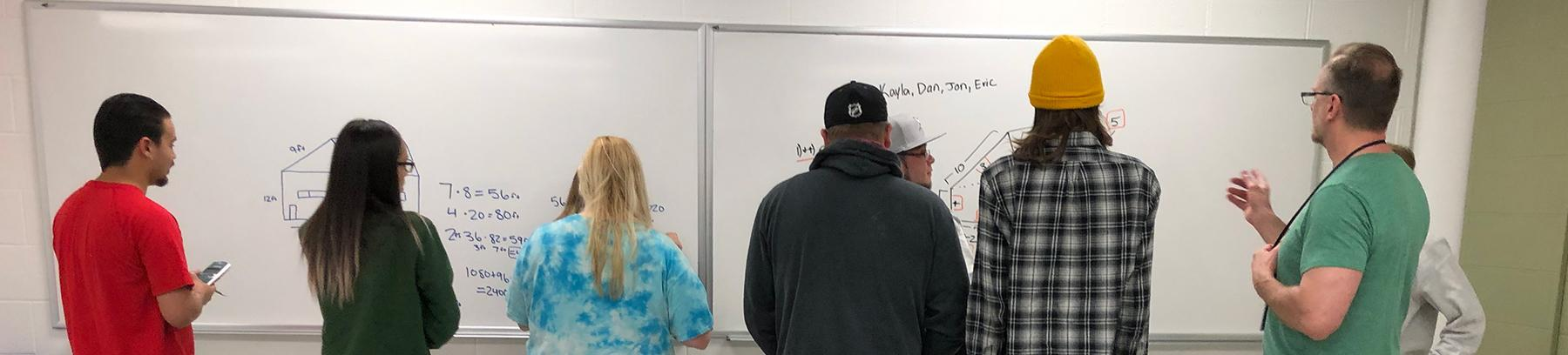 Students and instructor standing in front of a white board working on a math problem.
