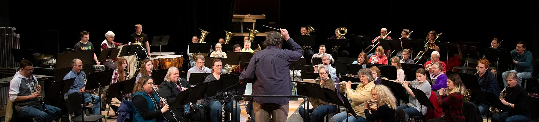 Wide shot of a band playing music with conductor leading