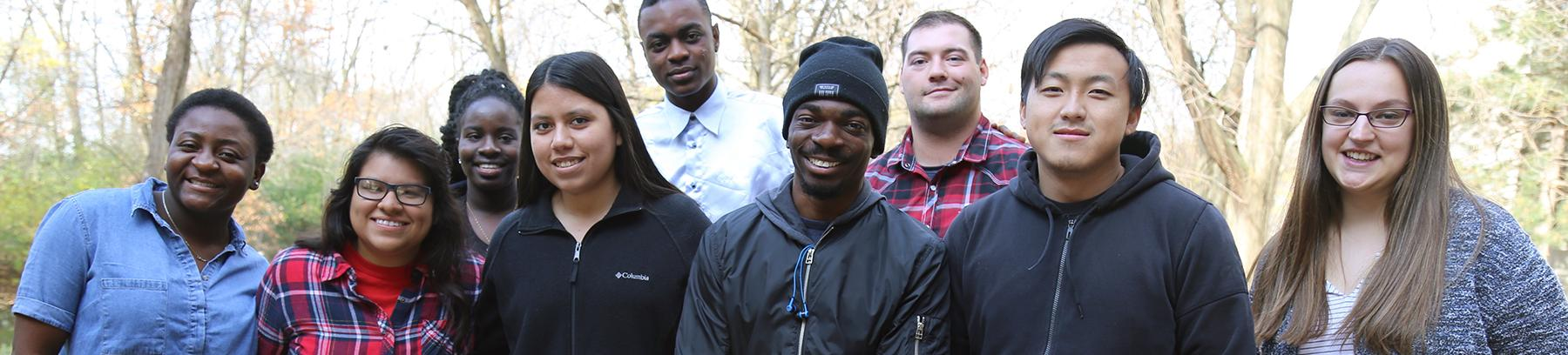 Diverse group of students outdoors in front of a background of trees.