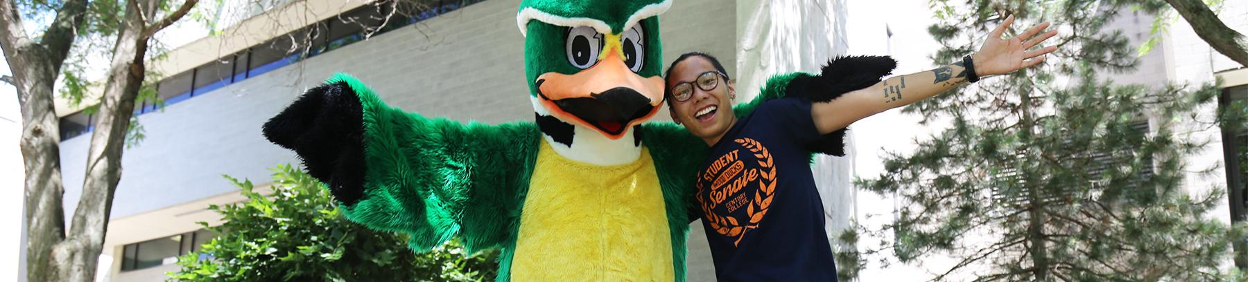 Student standing with Woody the Wood Duck, both with their arms out wide.