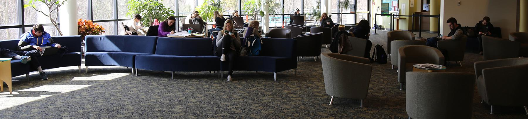 Students on devices in the West Campus common area.