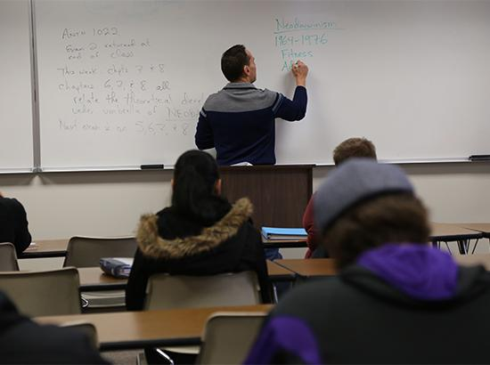 Instructor writing on a whiteboard and teaching to a group of students.