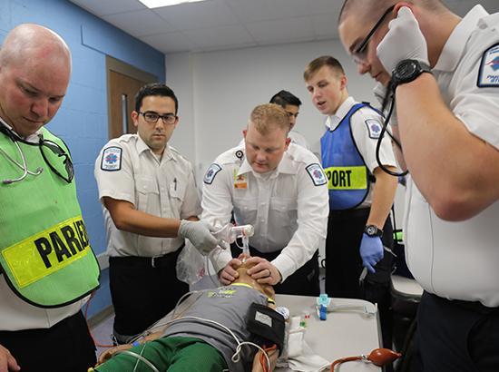 Five paramedics working on a CPR manikin.