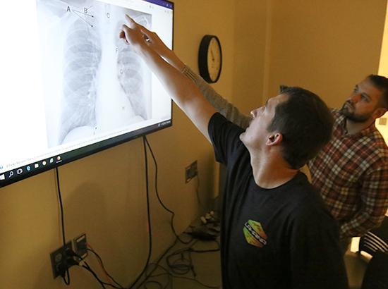 Man pointing at an X-Ray of a ribcage.