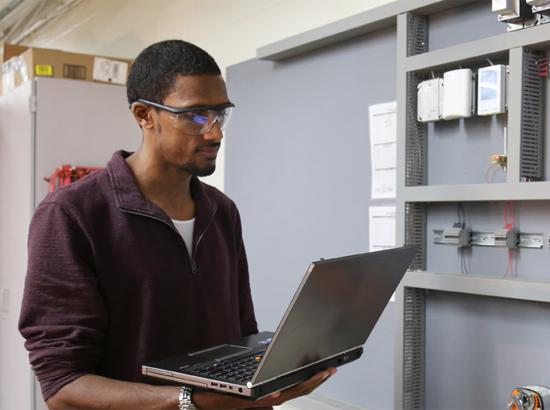 Student with safety glasses on holding computer.