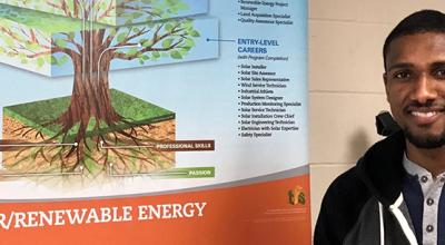 Portrait of Alcilito Almeida in front of the Solar and Renewable Energy career tree poster
