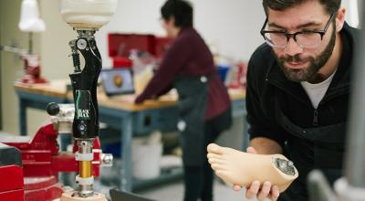 Student holding a prosthetic foot