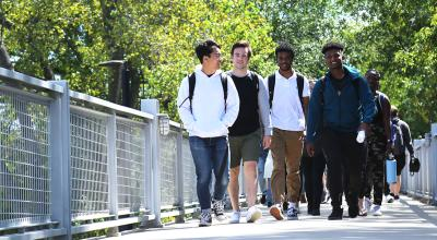 Four male students walking on the Century College bridge.