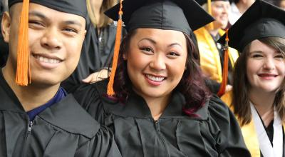 students in cap and gowns smiling